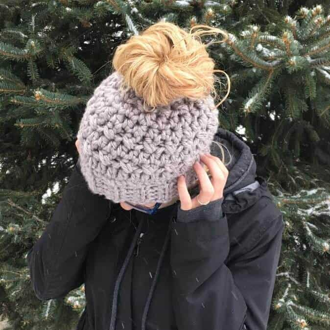 Photo showing the top view of the crocheted messy bun hat worn by a woman wearing a black jacket