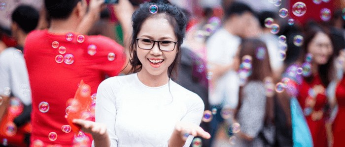 Photo of a woman wearing eyeglasses and white shirt enjoying bubbles