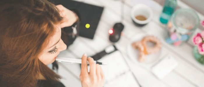 Top view photo of a woman holding a pen on her lips with a table full of stuff