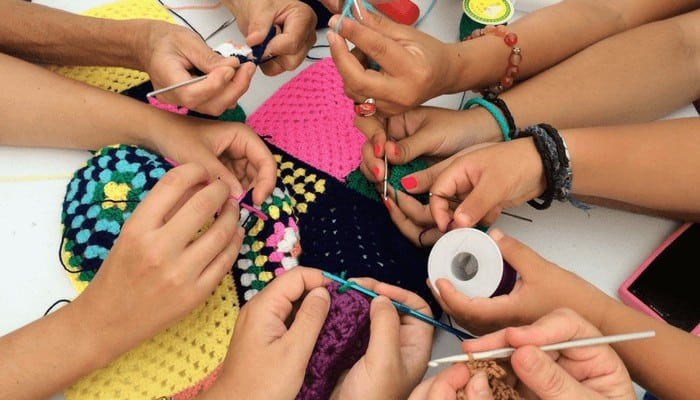 Photo of a group of hands crocheting