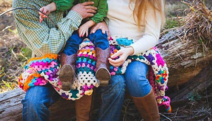 Photo of a family, their laps covered in a colorful crocheted blanket