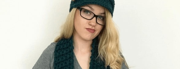Photo of a blonde woman wearing a crocheted hat and scarf on top of a gray shirt
