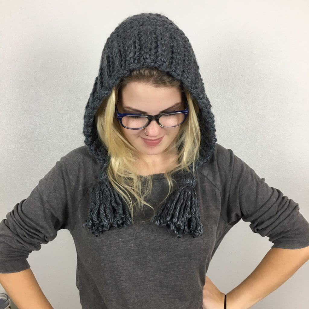 A blonde woman wearing the Chelsea Earflap Hat Crochet Pattern with white background