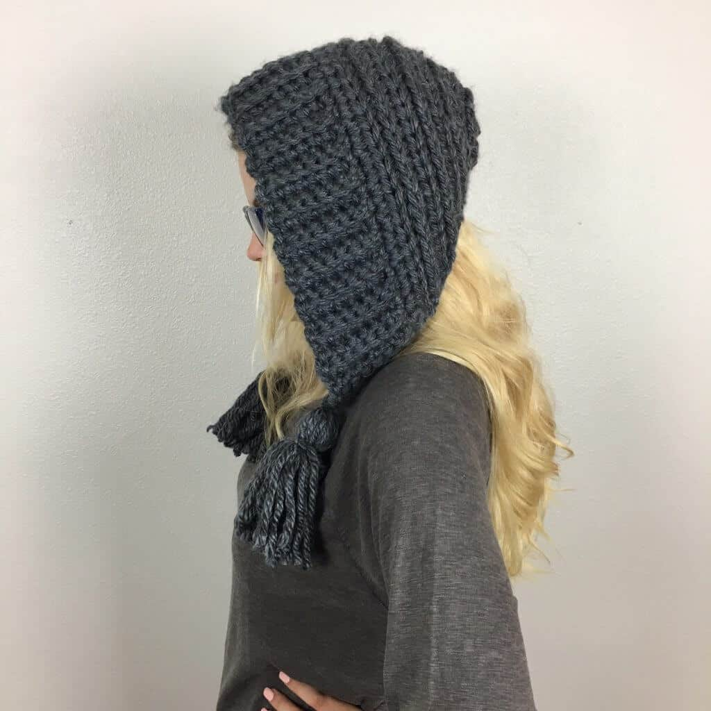Side view of the Chelsea Earflap Hat Crochet Pattern worn by a woman