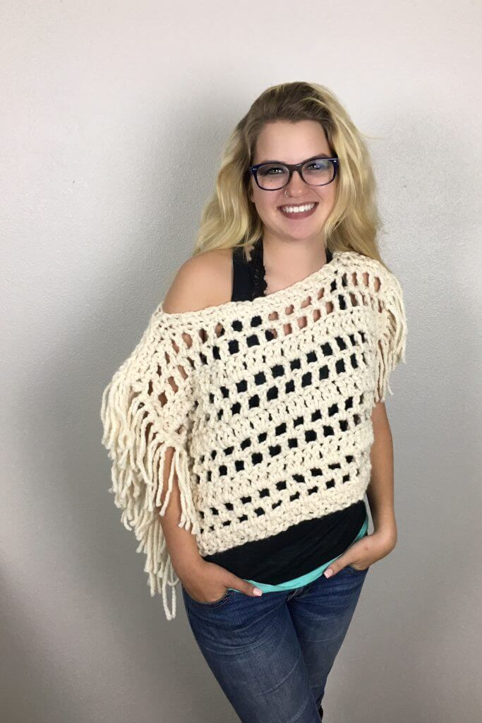 A blonde woman wearing the Santa Fe Fringy Boho Crop Top over a black sleeveless shirt