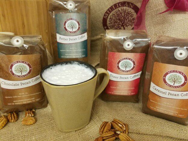 Photo of a mug of coffee and 4 bags of Pecan Coffee from Millican Pecan Company