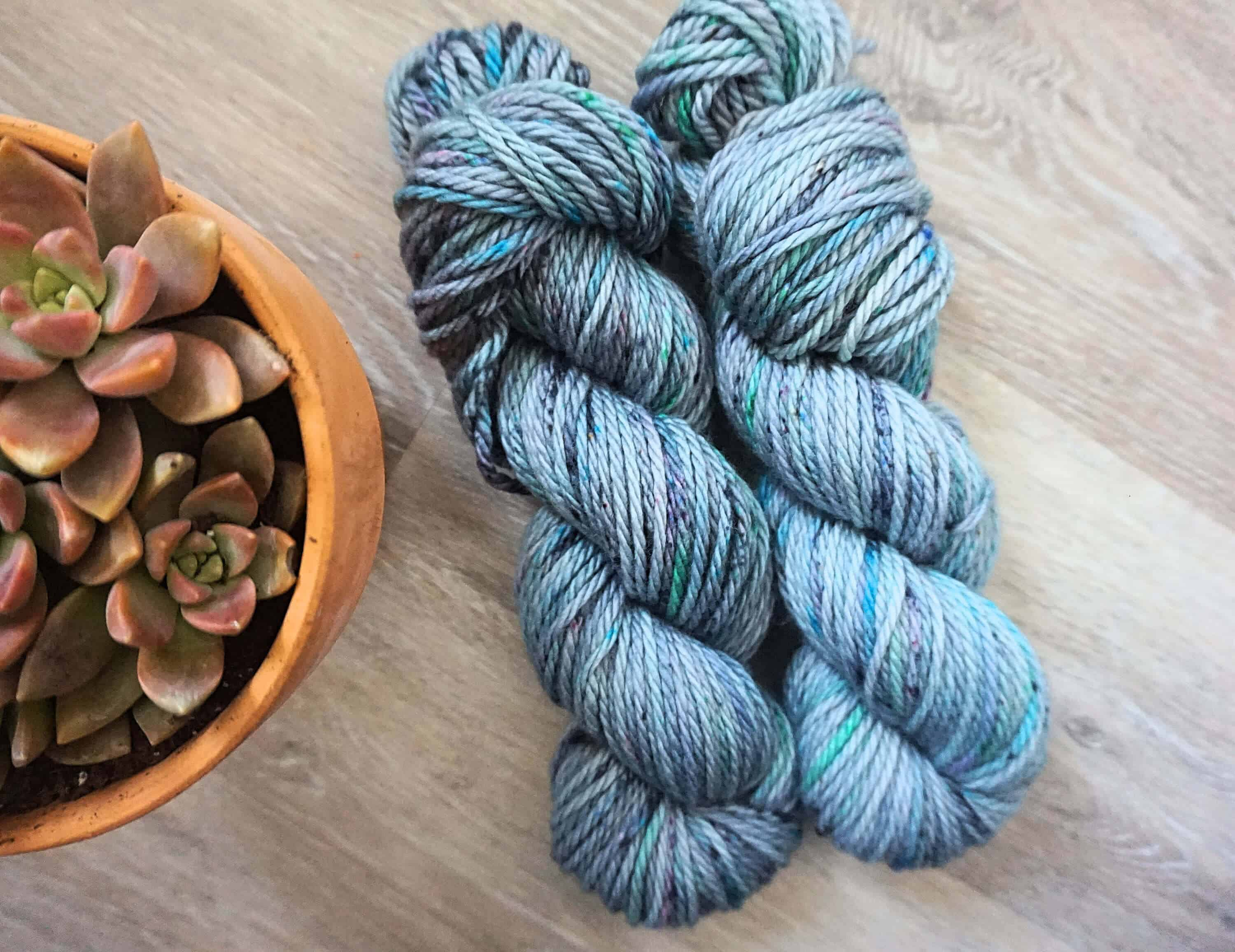 Image of 2 Bulky Merino Wool from Knit Coast Fibers with a pot of succulents at the left side