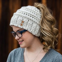 A woman wearing eyeglasses and the Beehive Messy Bun Hat Beanie