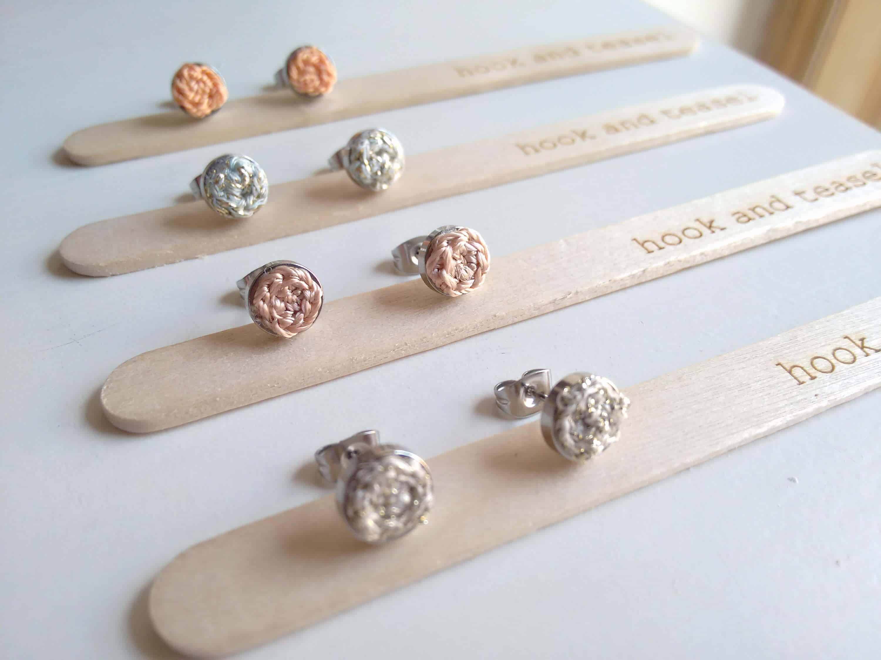 Photo of 4 pairs of earrings from Yarn and Teasel each pair on a popsicle stick