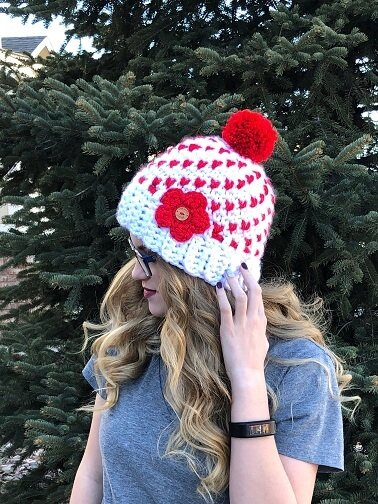 Valentine's day is coming and this hat full of hearts is the perfect accessory for the day of love and everyday! The Heartful Winter Hat is a women's hat that is meant to fit loosely. Worked by carrying the coordinating color behind the stitches, the double layer creates a warm hat for even the coldest of days. A quick and easy pattern, the fair isle style hat is worked in super bulky yarn and can be completed in just over an hour for a quick turnaround. Your customers and loved ones are going to want one in every color! The women's beanie pattern with hearts throughout is a written pattern with photo tutorials for the color changing stitches and the pompom. While the pattern indicates that it is for intermediate crocheters, once the color change is figured out, the hat is a breeze to make!