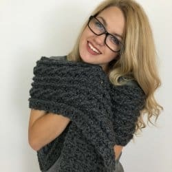 A blonde woman wearing eyeglasses and the crocheted Ardara Cable Scarf