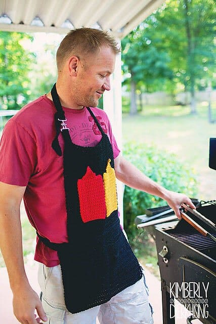 Photo of a guy grilling outdoors wearing the crocheted BBQ toolbelt apron