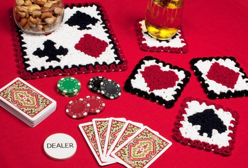 Photo of crocheted playing cards coasters on a red table with poker chips, playing cards, nuts, and drinks