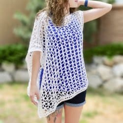 Photo of a woman wearing the crocheted Star-Spangled Ponchette on top of a blue shirt