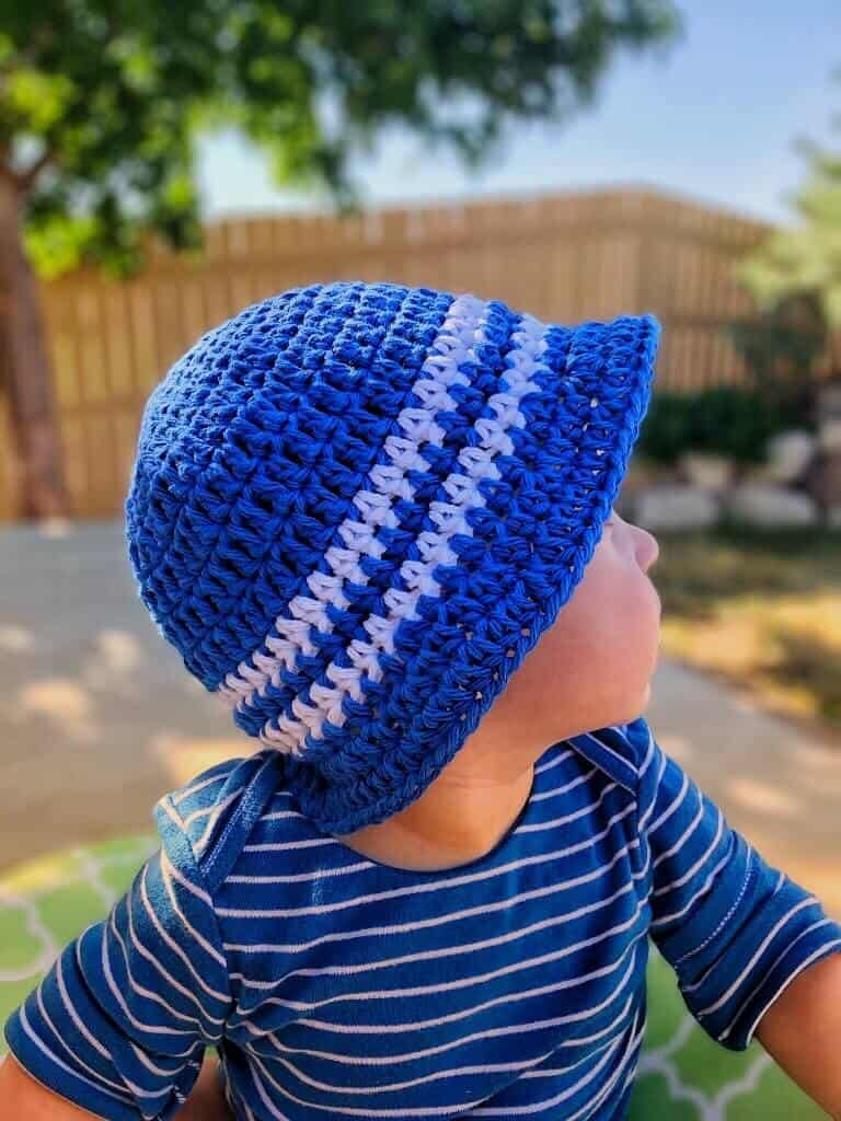 Blue with white stripes Sun and Sand Little Boys Bucket Hat worn by a kid with blue and white shirt looking away from the camera