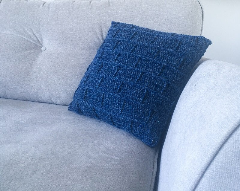 A simple but soft and unique building blocks throw pillow on the side of a sofa