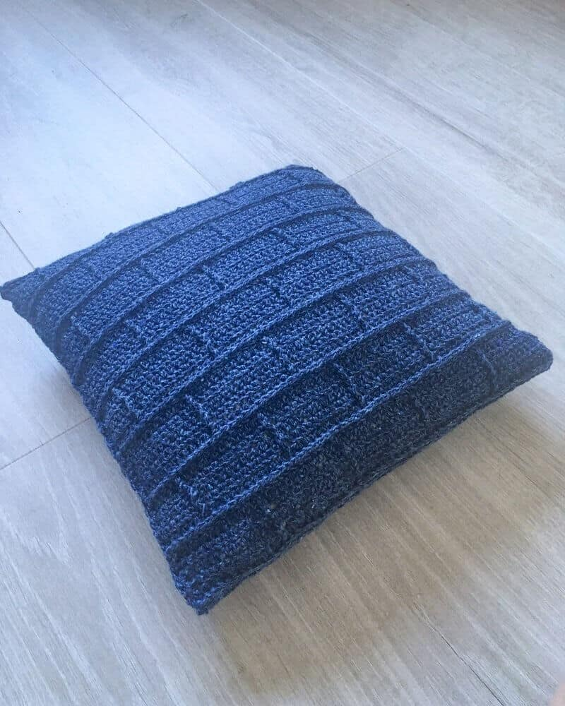 Photo of the crocheted blue throw pillow on a wooden floor