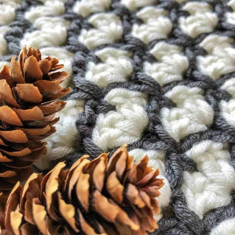 Close look at the stitches of the Sirena's winter cowl's shell stitch with pine cones