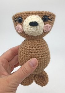 Photo of assemblying the crocheted Amigurumi Seal Pup held by a hand