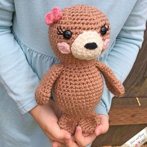Photo of the finished Amigurumi seal pup FREE crochet pattern held by a little girl wearing a blue dress