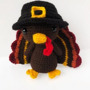 Photo of the crocheted Thanksgiving Turkey wearing a black hat with a yellow hollow square design at the middle