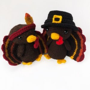 Photo of 2 crocheted amigurumi turkey, one wearing a red headband and the other one wearing a black hat