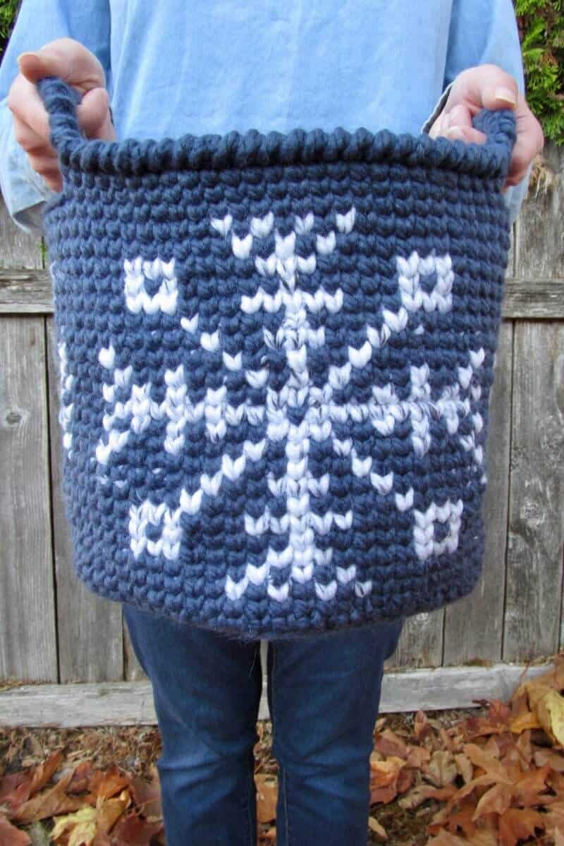 Photo of the blue Snowflake Tapestry Basket held by two hands