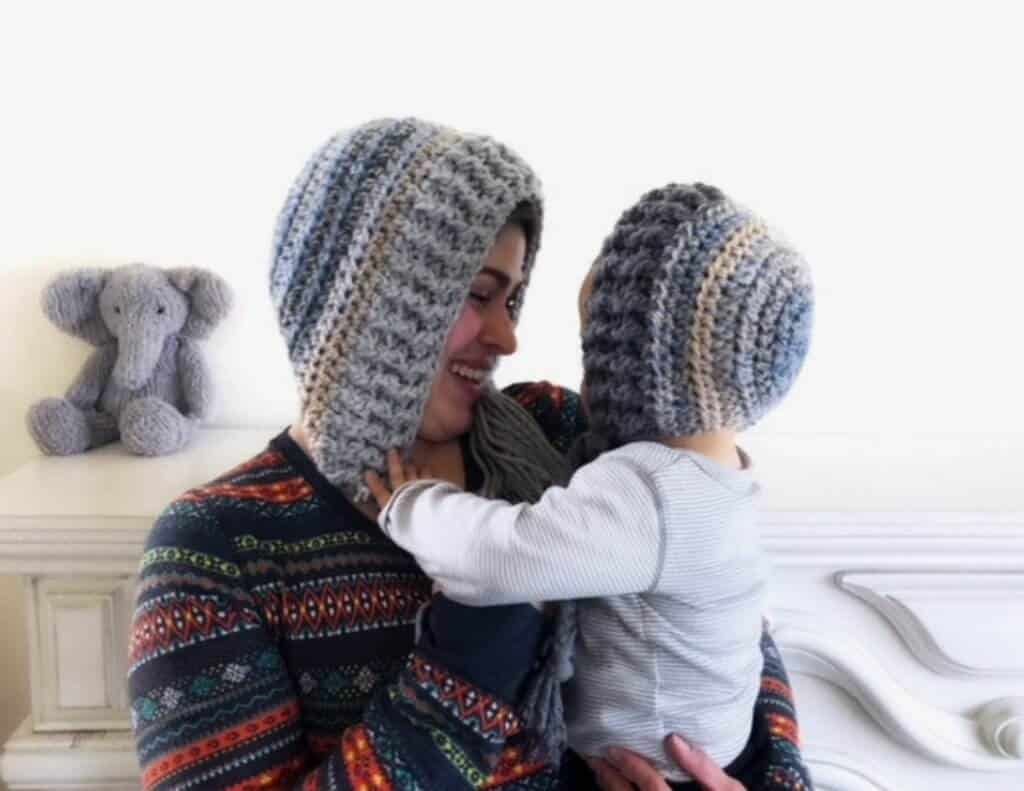 A mother and carrying her child both wearing the Snow Day Hood winter hat with a stuffed elephant at the back