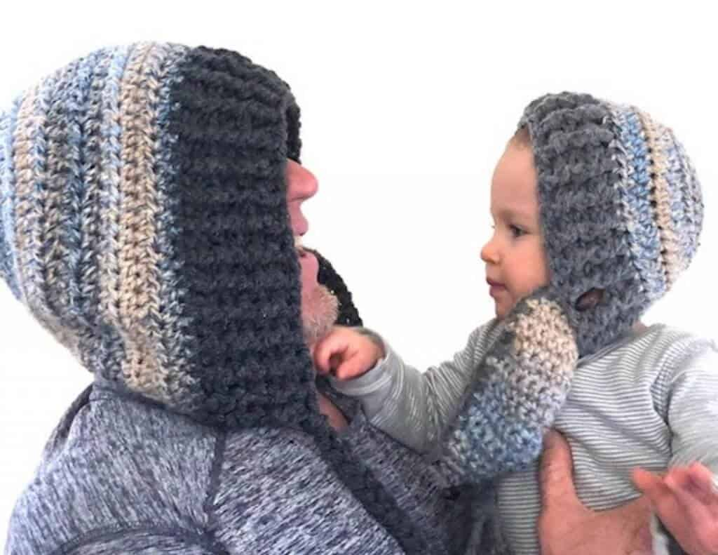 A father and child photo while wearing the crocheted Snow Day Hood winter hats with detachable mask