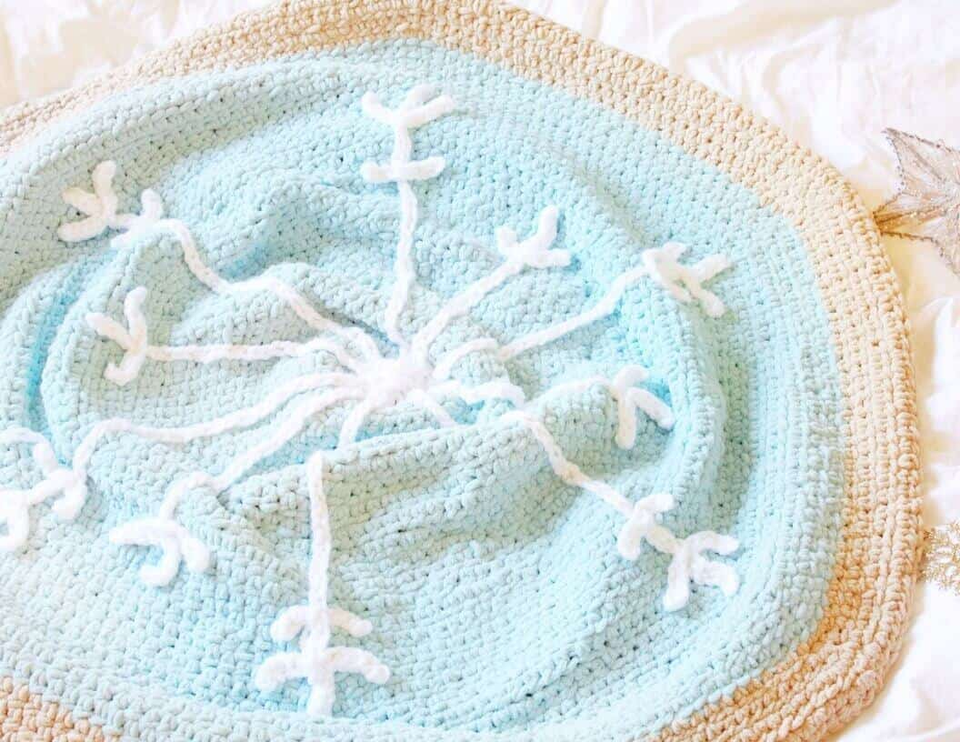 Photo of the crocheted blanket with a snowflake design at the middle