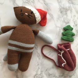 Photo of the crocheted Chrissie the Christmas Cat wearing a Santa hat with a cute tree and small pouch