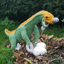 Photo of a crocheted mommy Therizinosaurus dinosaur protecting her eggs