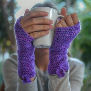 Photo of a person wearing the fingerless version of the Easy Fit Lite Gloves with small flowers while holding a mug