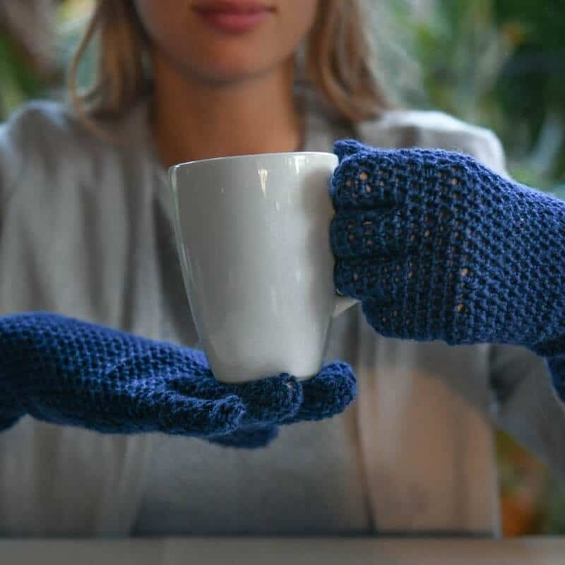 Photo of a person wearing a crocheted blue Easy Fit Lite Gloves with fingers