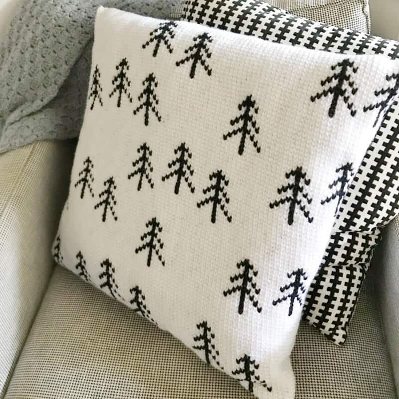 A photo of the crocheted Nordic Tree Pillow on a couch
