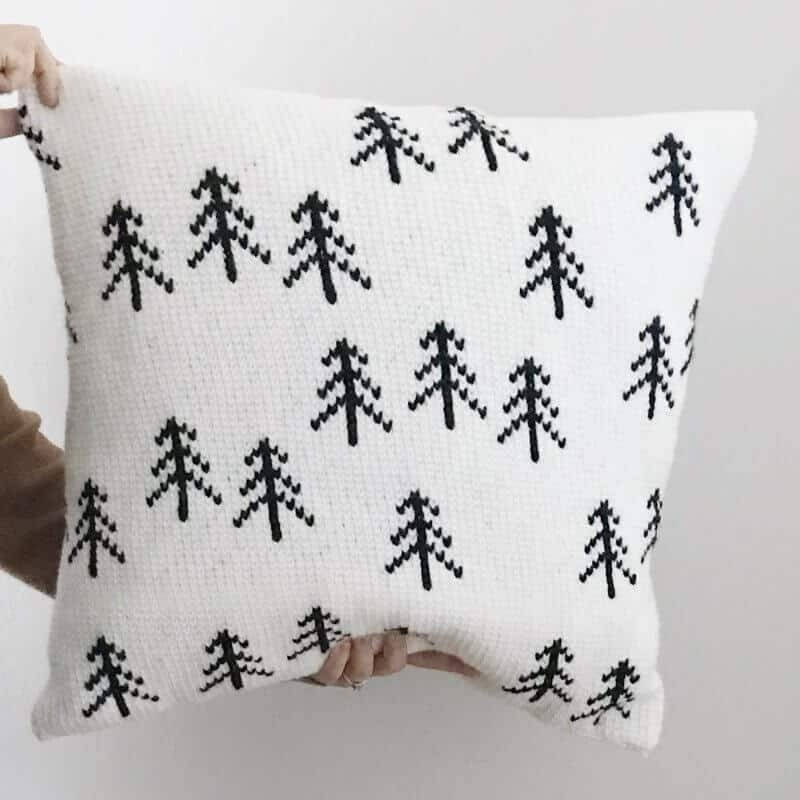 Closer look at the Nordic Tree Pillow held by 1 pair of hands