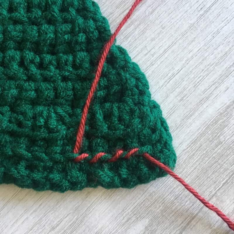 Tutorial image for adding the garland on the crocheted Christmas tree wall hanging