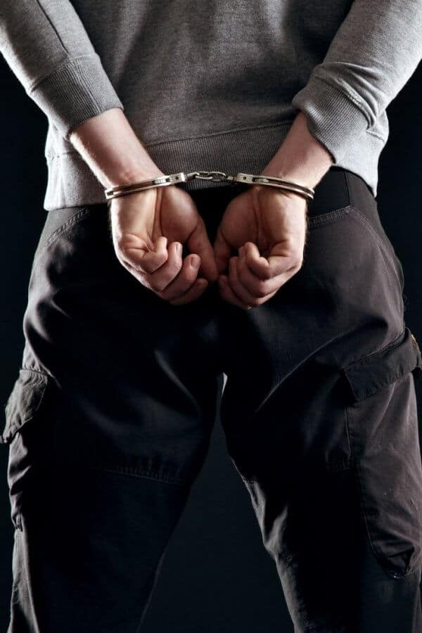a rear-view photo of a man wearing a grey shirt and black pants with his hands in handcuffs behind his back.