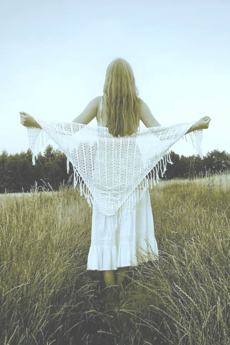 image of a woman in a field, from the rear, wearing a white crochet shawl